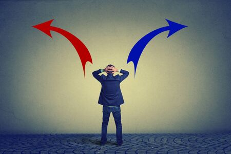 Photo pour Rear view of business man standing in front of wall hands on head wondering which way to go. Full length businessman facing wall. Confused man looking at drawn arrow signs red and blue making decision - image libre de droit