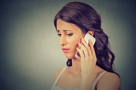 Concerned young woman talking on mobile phone