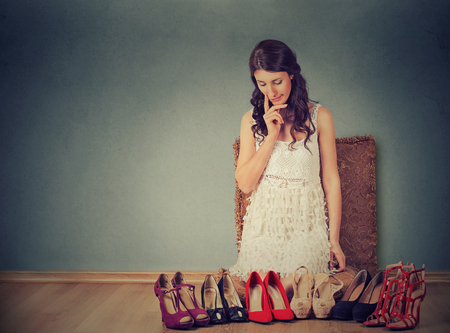 Woman making decisions picking up the right pair of high heel shoes