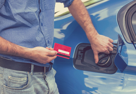 Photo pour Man with credit card opening fuel tank of his new car - image libre de droit