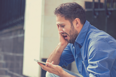 Photo pour Desperate sad handsome young man looking at bad text message on his mobile phone sitting outside corporate office on a summer day. Human emotions reaction - image libre de droit