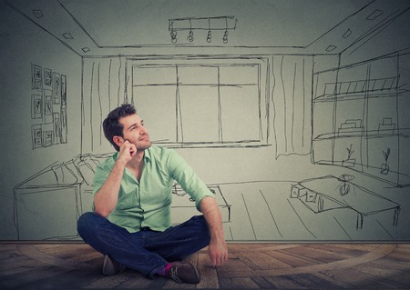Photo pour Dreaming man isolated over drawn living room background. Young handsome guy thinking of furnishing his new apartment. - image libre de droit