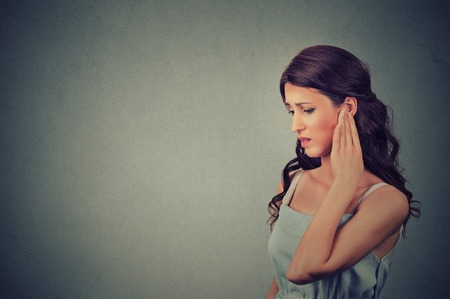 Foto für Tinnitus. Side profile sick young woman having ear pain touching her painful head temple isolated on gray wall background with blank copy space - Lizenzfreies Bild