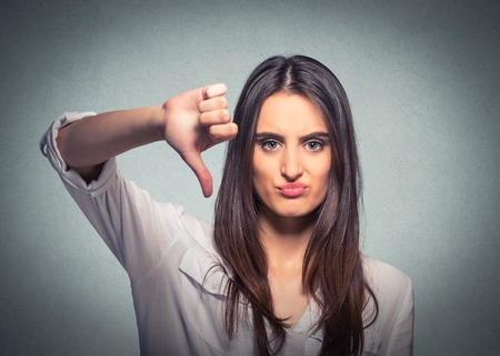 Unhappy woman giving thumb down gesture looking with negative expression and disapproval on gray background