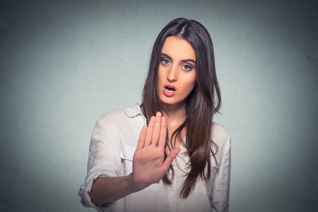 Young annoyed angry woman with bad attitude giving talk to hand gesture with palm outward isolated grey wall background. Negative human emotion face expression feeling body language