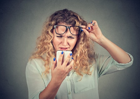 Photo pour Closeup portrait headshot young woman with glasses having trouble seeing cell phone has vision problems. Bad text message. Negative human emotion facial expression perception. Confusing technology - image libre de droit