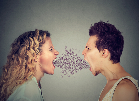 Foto de Side profile angry young couple man and woman screaming face to face with alphabet letters coming out of open mouth. Negative face expression emotion - Imagen libre de derechos