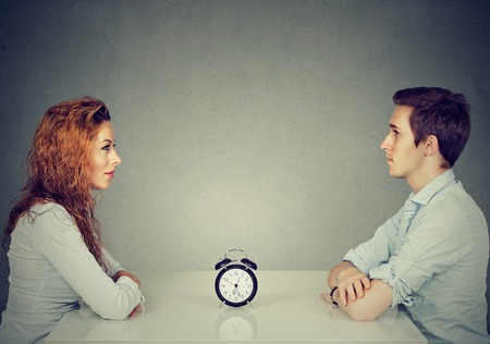 Foto de Speed dating. Man and woman sitting across from each other at table with alarm clock in-between - Imagen libre de derechos