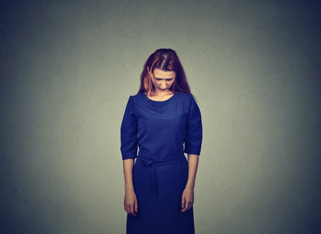 Sad shy insecure young woman standing looking down avoiding eye contact isolated on gray wall background