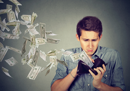 Photo pour Sad man looking at his wallet with money dollar banknotes flying out away - image libre de droit