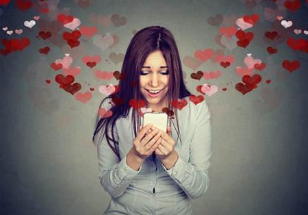 Foto de Portrait young beautiful woman sending receiving love sms text message on mobile phone with red hearts flying up isolated on gray wall background. Human emotions - Imagen libre de derechos