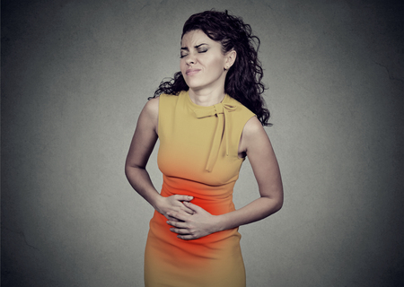 Young woman with hands on stomach having bad aches pain isolated on gray background. Food poisoning, cramps. Negative emotion face expression health problems