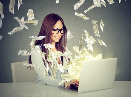 Photo for Professional smart young woman using a laptop building online business making money dollar bills cash coming out of computer. Beginner IT entrepreneur success economy concept - Royalty Free Image