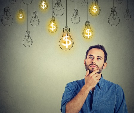 Photo for Portrait thinking handsome young man looking up at many dollar idea light bulbs above head - Royalty Free Image