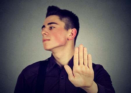 Annoyed man with bad attitude giving talk to hand gesture isolated gray wall background. Focus on palm. Negative human emotion face expression feeling body language reaction