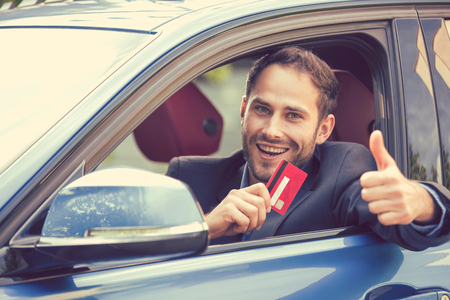 Foto de Happy smiling man sitting inside his new car showing credit card giving thumbs up. Personal transportation auto purchase concept - Imagen libre de derechos