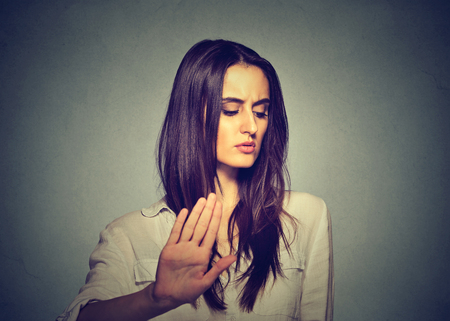 Upset angry woman giving talk to hand gesture with palm outward isolated on gray wall background. Negative human emotion body language
