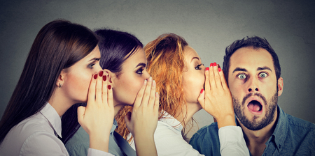 Foto de Three young women whispering each other and to the shocked astonished man in the ear. Word of mouth communication concept. Human emotion face expression reaction  - Imagen libre de derechos