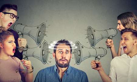 Photo for Group of people screaming in megaphones at scared guy - Royalty Free Image