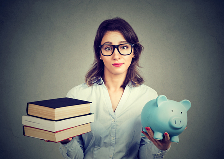 Student loan concept. Young woman with stack pile of books and piggy bank full of debt rethinking future career path