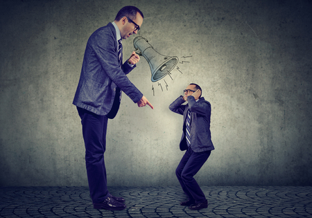 Photo pour Angry business man boss screaming at himself small in megaphone - image libre de droit