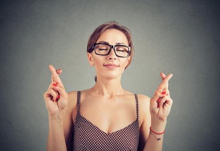 Photo pour Cute young woman in glasses crosses fingers, making a wish - image libre de droit