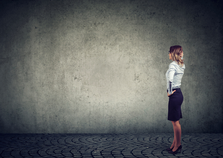 Foto de Rear view of business woman standing by the wall with hand on head wondering what to do next being challenged. Full length of businesswoman facing the obstacle - Imagen libre de derechos