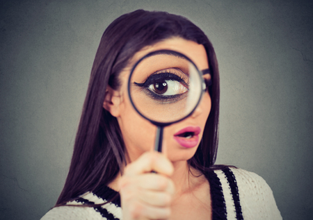 Curious young woman looking through a magnifying glass
