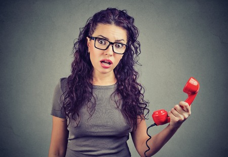 Photo for Resentful shocked young woman looking in disbelief holding telephone handset - Royalty Free Image