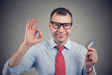 Photo pour Cheerful happy business man with credit card showing Ok sign on gray background - image libre de droit