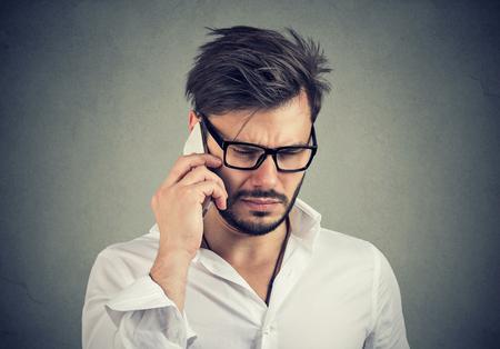 Photo pour Business man with sad expression talking on mobile phone looking down - image libre de droit