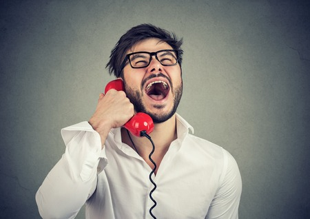 Photo pour Funny guy on the red telephone - image libre de droit