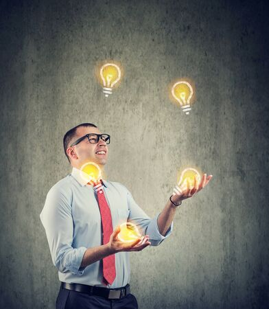 Photo for Young businessman juggling with new ideas light bulbs - Royalty Free Image