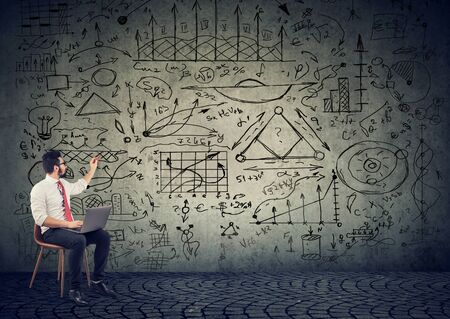 Photo pour Businessman with computer drawing business plan strategy on the wall - image libre de droit