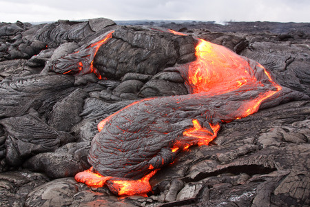 Lava loses heat rapidly and its surface turns black and is pushed into wrinkles by moving interior. Kilauea volcano, Pu'u O'o vent.