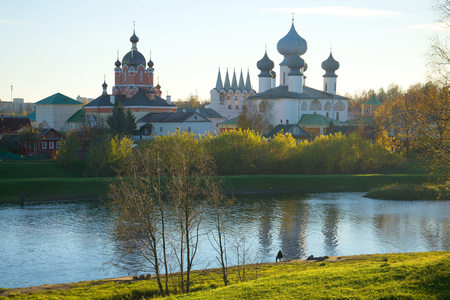 October evening on the Tikhvinka River. View of the temples of the Tikhvin Monastery, Russia