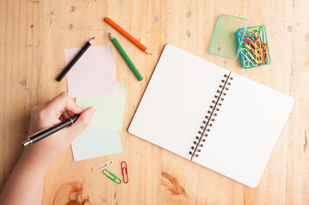 Notebook and sticky paper, paper clip, color pencil, and pen with female left hand on wood table