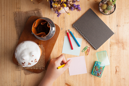Woman left hand writing on sticky paper with blank space for text or message on wood table with notebook, paper clip, color pencil, and pen in cafe