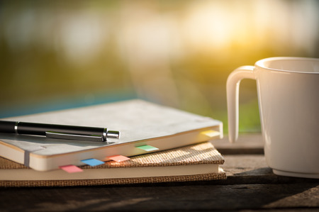 Pen, notebooks, and coffee cup on rustic wood table at outdoor area with morning scene in summer time