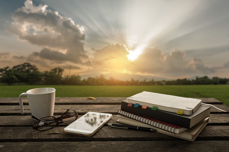 Photo pour Smartphone, notebooks, coffee cup, glasses, and pen put down on outdoor wood table in morning time on weekend. Freelance business working concept - image libre de droit