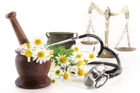 Stethoscope on a white background and chamomile