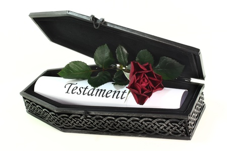 a small coffin with roses and Testament