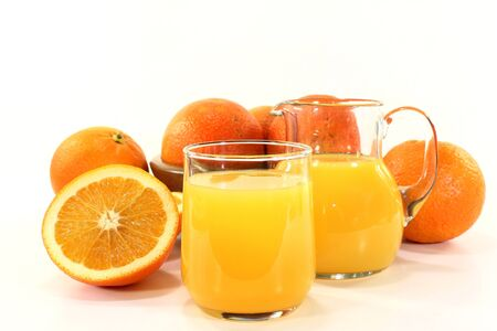 a glass of orange juice and fresh oranges