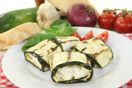 stuffed courgette rolls and tomatoes on a white plate