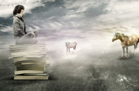 Photo pour Girl sitting on books and waching at two magic horses - image libre de droit