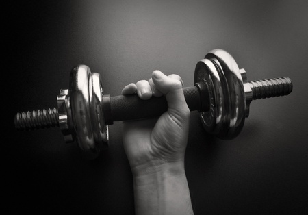 Young man working out with a  dumbbell-NOTE:Grain and contrast was added