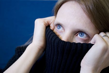 Girl with blue eyes covering her face with a sweater