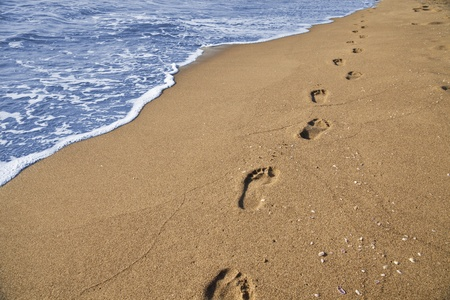 Footsteps of a man who walks on the beach by the sea