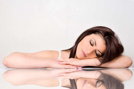 Foto per Beautiful face skincare bellezza donna sdraiata con riflessione a specchio isolato su sfondo bianco - Immagine Royalty Free