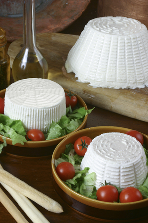 selection of italian fresh cheese and ricotta on wood background